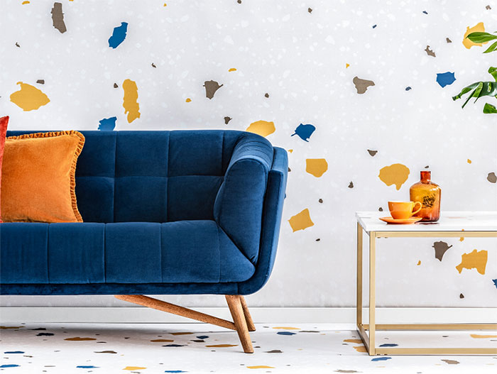 Modern blue loveseat with orange throw pillows and customizable Memphis design inspired wallpaper and flooring.